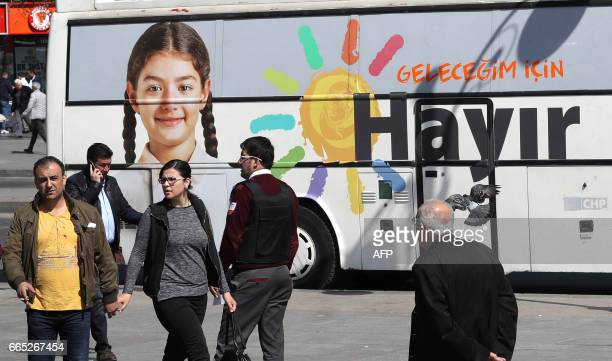 People walk past a poster reading 'no' pasted on a bus in Ankara on April 6 ten days ahead of the referendum on whether to change the current...