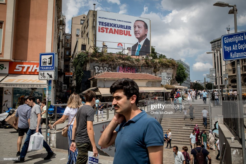 People walk past a poster showing the portrait of Turkey's President Recep Tayyip Erdogan and the words translating to 'Thank you Istanbul' on July 9, 2018 in Istanbul, Turkey. President Erdogan was sworn in during a parliamentary meeting and later an inauguration ceremony attended by a number of foreign leaders and dignitaries. President Erdogan secured another five year term and increased powers after winning 52.5percent of the vote in the June 24 snap presidential and parliamentary elections. Under the new presidential system Erdogan will have the power to dissolve parliament, appoint or remove vice-presidents, ministers, judges and high level officials as well as issue executive decrees and lift or impose a state of emergency. Turkey has been under a state of emergency since the July 2016 failed coup attempt and since then the government has arrested, sacked and detain over 100,000 people said to be supporters of religious leader Fethullah Gulen. Erdogan announced that the current state of emergency would be lifted on July 18, 2018.