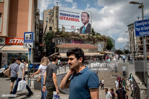 People walk past a poster showing the portrait of Turkey's President Recep Tayyip Erdogan and the words translating to 'Thank you Istanbul' on July 9...