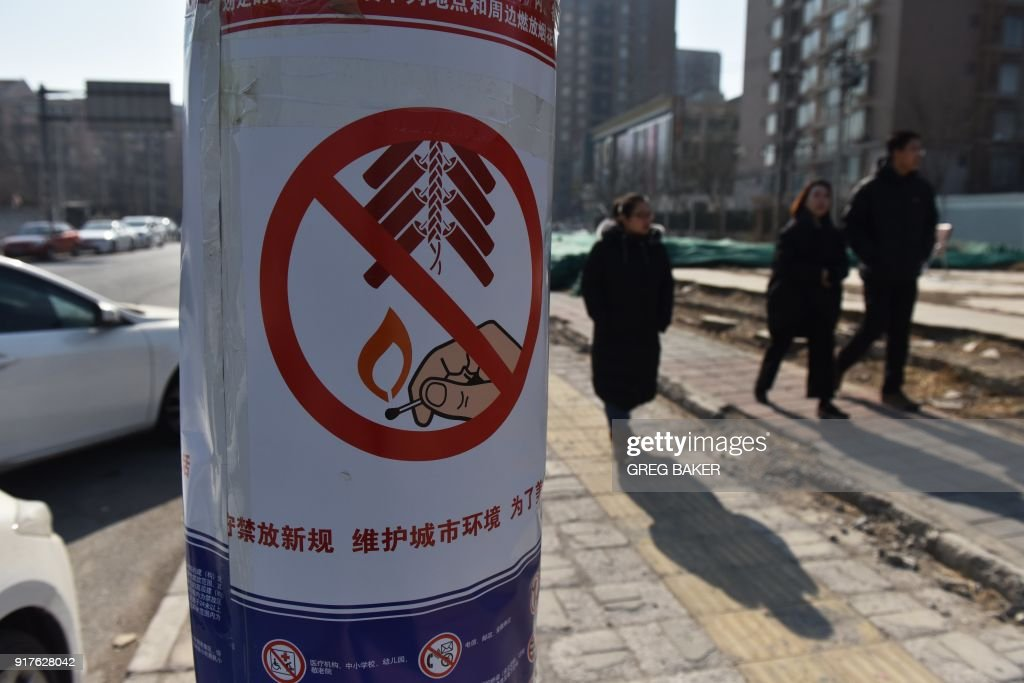 People walk past a poster with details about a fireworks ban near a stall selling fireworks on the outskirts of Beijing, in the build-up to Lunar New Year celebrations on February 13, 2018. Beijing has banned fireworks in central city areas during the Lunar New Year holiday in an effort to reduce air pollution and injuries. Residents will be permitted to set off fireworks outside the city's 5th Ring Road. /