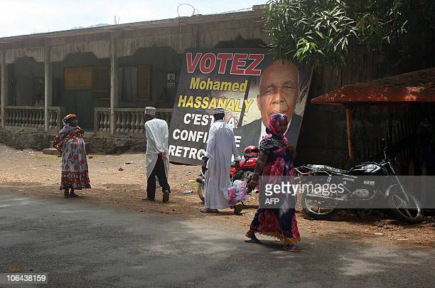People walk past a presidential campaign poster for Mohamed Hassanaly on November 2 2010 in the Comoros Island of Moheli The governors of the...