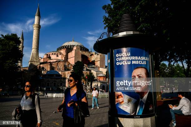 People walk past a presidential campaign poster showing incumbent Turkish President in front of the Hagia Sophia museum in Istanbul on June 19 2018...