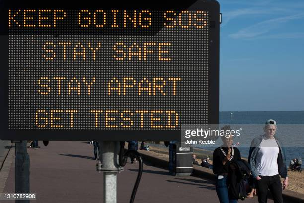"""People walk past a public safety notice saying """"Keep going SOS, Stay safe, Stay apart, Get tested"""" on a warm sunny Easter Sunday at Westcliff beach..."""