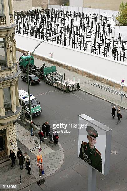 People walk past a rebuilt section of the Berlin Wall and crosses that commemorate its victims on the day of the memorial's unveiling on October 31...