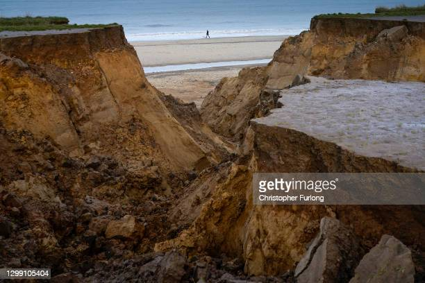 People walk past a recent landslip on the cliff edge and beach in the village of Happisburgh on January 27, 2021 in Happisburgh, England. Erosion of...