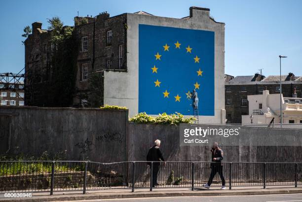 People walk past a recently painted mural by British graffiti artist Banksy depicting a workman chipping away at one of the stars on a European Union...