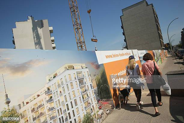 People walk past a residential property development in Kreuzberg district in the city center on May 11 2016 in Berlin Berlin Berlin is drawing tens...