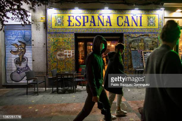 People walk past a restaurant on the first night of a countrywide curfew on October 25, 2020 in Madrid, Spain. Spain has declared a national state of...
