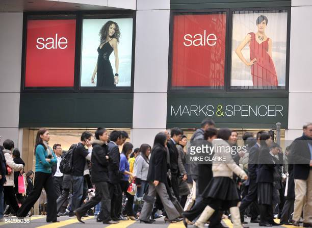 People walk past a retail outlet of British retailer Marks Spencer in Hong Kong on January 15 2009 The retailer an icon and key barometer of consumer...