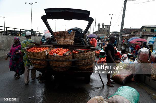 People walk past a rickety truck overloaded with tomatoes in a sparsely attended Mile 12 Market in Lagos, on April 6, 2020. - The lockdown of Lagos,...