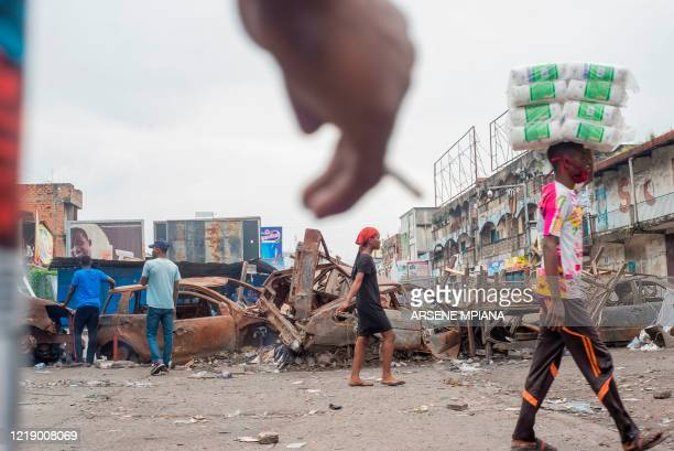 People walk past a road barricade at the Kinshasa Grand market on June 9 during a demonstration where demonstrators ask for the re-opening of the...