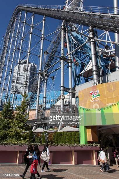 People walk past a roller coaster at Tokyo Dome City an entertainment area in Bunkyo ward Tokyo Japan November 3 2017