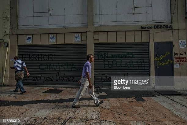 People walk past a row of closed stores in the usually busy downtown shopping district in Caracas Venezuela on Tuesday March 22 2016 Venezuela shut...