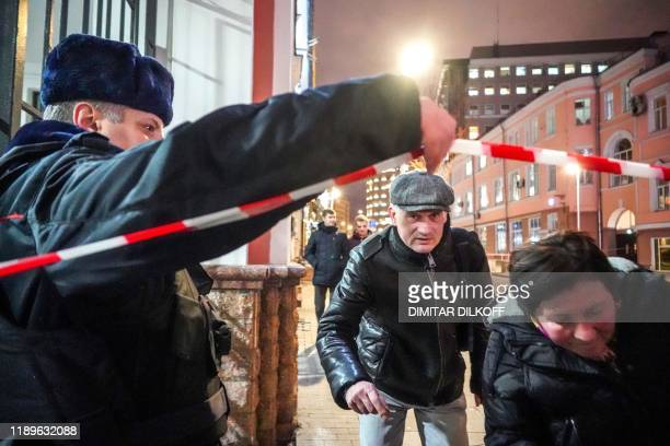 People walk past a Russian police officer next to the FSB security service's office in Moscow on December 19 2019 A member of the Russian FSB...