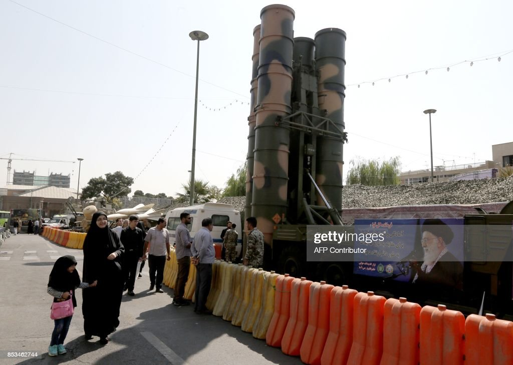 People walk past a Russian-made S-300 air defence system
