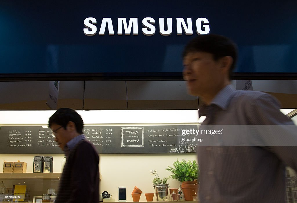 People walk past a Samsung Electronics Co. logo displayed at the company's Seocho office building in Seoul, South Korea, on Wednesday, Dec. 5, 2012. Samsung Electronics Co. promoted Lee Jae Yong to vice chairman, putting him a step closer to succeeding his father as leader of the world's biggest maker of televisions and mobile phones. Photographer: SeongJoon Cho/Bloomberg via Getty Images