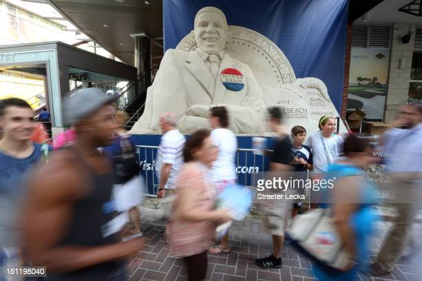 People walk past a sand sculpture of Barack Obama along the streets of uptown Charlotte ahead of the Democratic National Convention on September 3,...