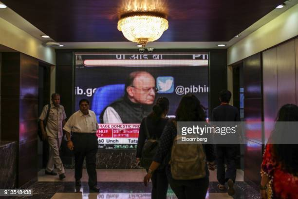 People walk past a screen showing an image of Arun Jaitley India's finance minister during a budget news report at the Bombay Stock Exchange in...