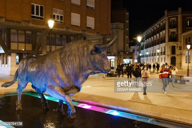 People walk past a sculpture depicting a fighting bull in downtown Burgos, in Castilla and Leon region, before the entry into force of a curfew in...