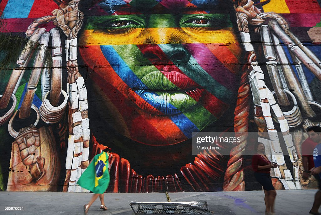 People walk past a section of a mural depicting an indigenous face created by Brazilian graffiti artist Eduardo Kobra and assistants in the revamped Port District on August 4, 2016 in Rio de Janeiro, Brazil. The 32,000-square-foot mural, titled 'We Are All One', was painted to represent cultural diversity across continents. The start of the Rio 2016 Olympic Games on August 5.