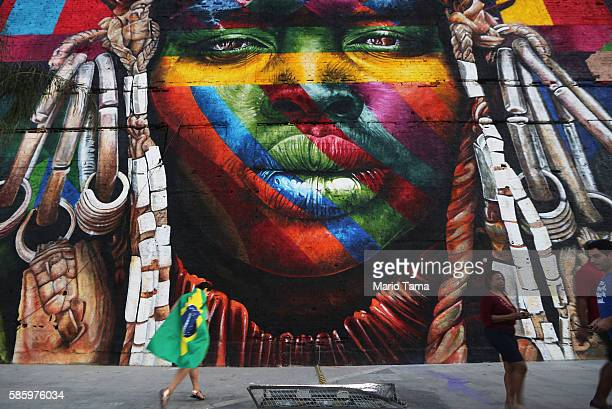 People walk past a section of a mural depicting an indigenous face created by Brazilian graffiti artist Eduardo Kobra and assistants in the revamped...