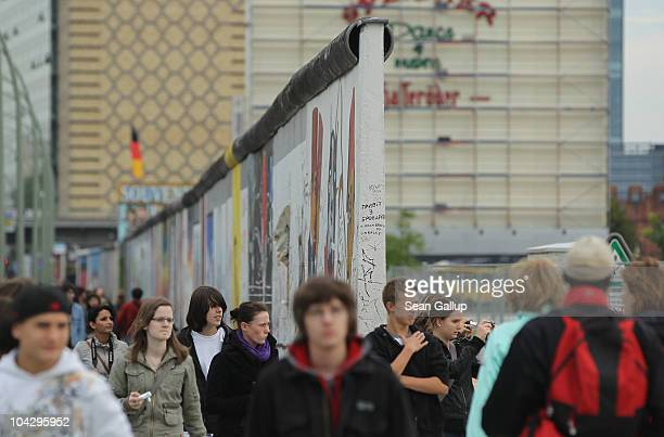People walk past a section of the former Berlin Wall called the East Side Gallery on September 20 2010 in Berlin Germany Germany will mark 20 years...