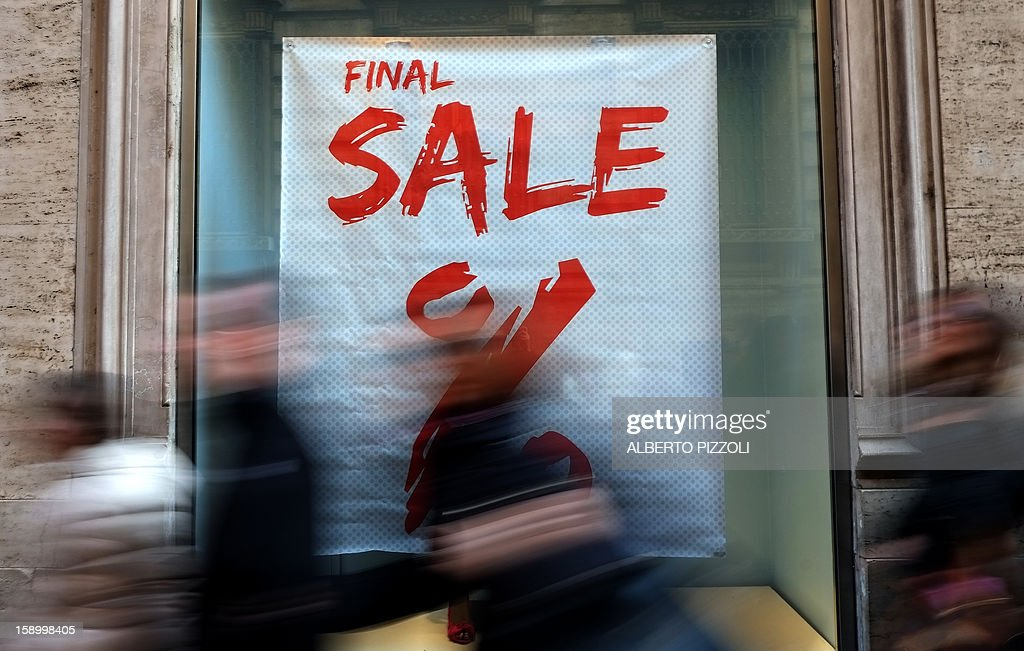 People walk past a shop advertising its sale, on January 5, 2013 during the first day of sales in Rome.