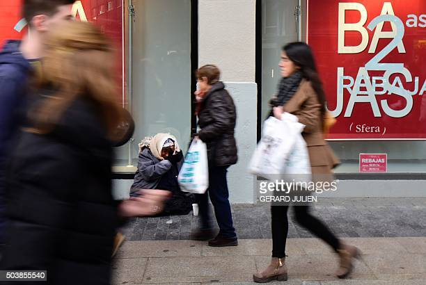 People walk past a shop window announcing the start of the winter sales as a beggar sits on the street in Madrid on January 7 2016 AFP PHOTO/ GERARD...