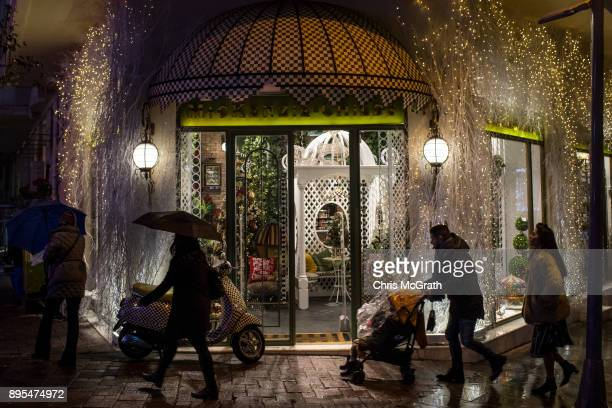 People walk past a shop window decorated in Christmas decorations on December 19 2017 in Istanbul Turkey Some luxury brands shopping malls and retail...