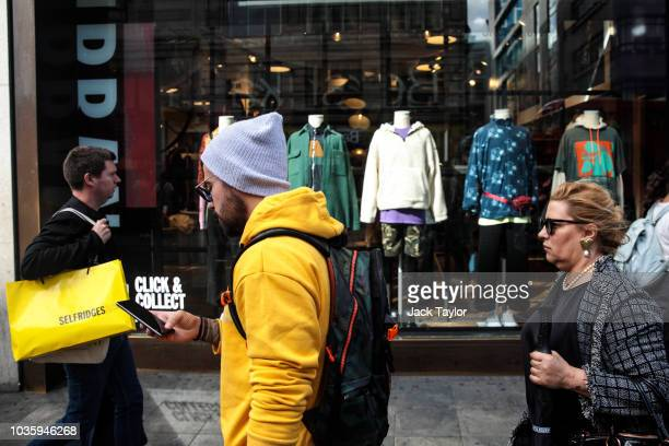 People walk past a shop window display on Oxford Street on September 19 2018 in London England UK inflation increased from 25% in July to 27% in...