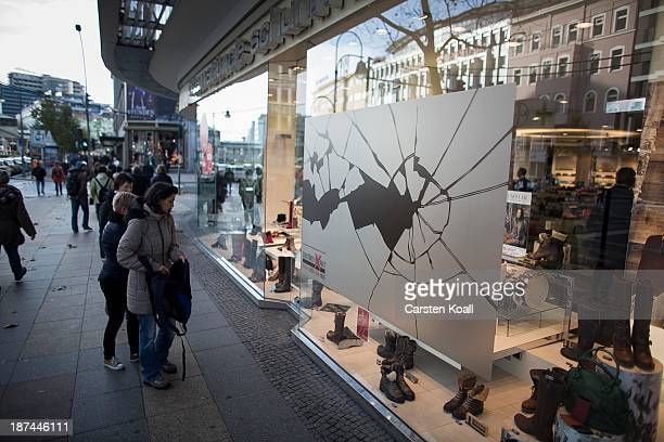 People walk past a shop window made to look like it has been smashed to commemorate the 75th anniversary of the Kristallnacht pogroms on November 9...
