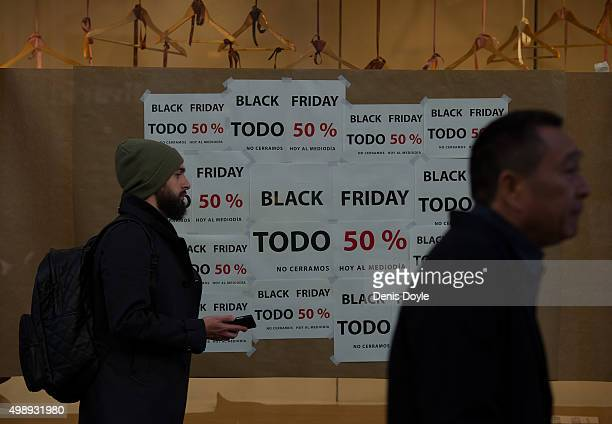 People walk past a shopfront advertising 'Black Friday' discounts on November 27 2015 in Madrid Spain Originating in the USA as a sales day following...