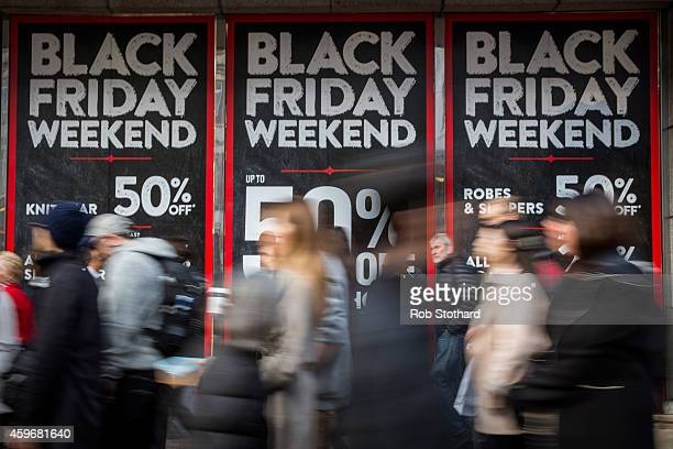 People walk past a shopfront on Oxford Street advertising 'Black Friday' discounts on November 28 2014 in London England Originating in the USA as a...