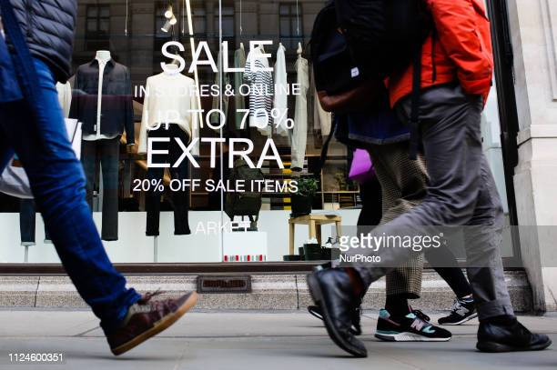 People walk past a sign advertising discounts in a branch of clothing retailer Arket on Regent Street in London England on February 9 2019 February...