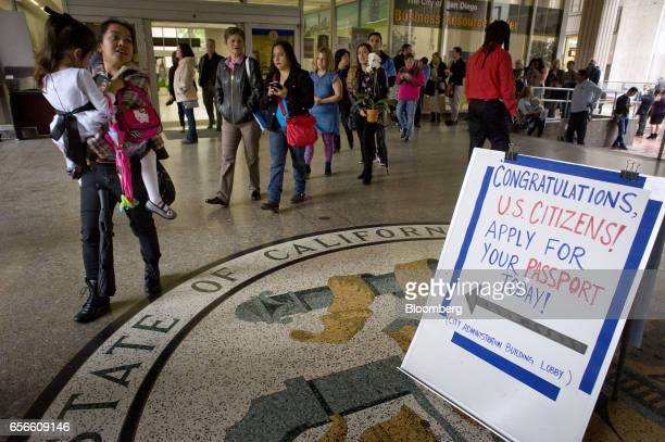 People walk past a sign directing citizens to apply for US passports while waiting in line to enter a naturalization ceremony in San Diego California...