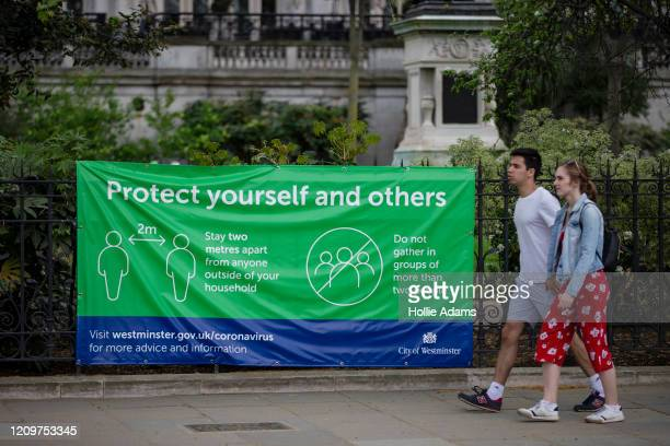 People walk past a sign displayed outside Whitehall Gardens on April 12 2020 in London England Public Easter events have been cancelled across the...