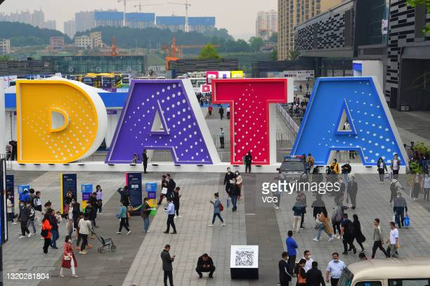 People walk past a sign during China International Big Data Industry Expo at Guiyang International Conference and Exhibition Center on May 26, 2021...
