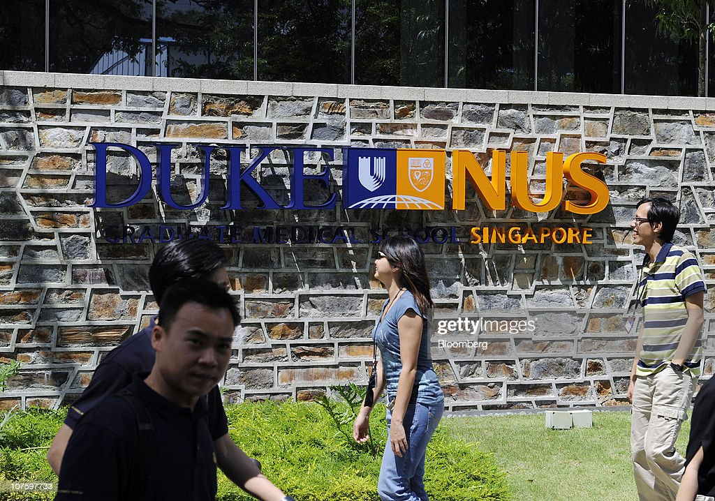 People walk past a sign for the Duke-NUS (National University of Singapore) Graduate Medical School in Singapore, on Monday, Dec. 6, 2010. Yale University may join Duke University, the University of Chicago, Imperial College London and France's Insead among colleges to set up a campus in Singapore, a nation of 5 million people with a land mass smaller than New York City. The city-state wants to attract 150,000 international students by 2015 as it seeks to boost the contribution education makes to gross domestic product to 5 percent from 3.2 percent last year and 1.9 percent in 2000. Photographer: Munshi Ahmed/Bloomberg via Getty Images