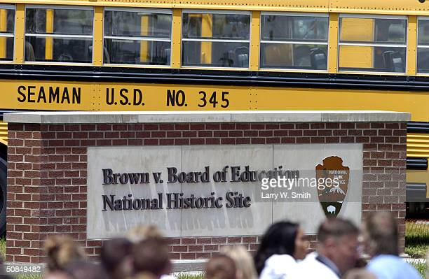 People walk past a sign in front of the Monroe Elementary School on the 50th anniversary of the US Supreme Court decision in the case of Oliver L...