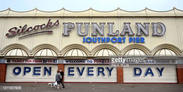 """People walk past a sign reading """"Open Every Day"""" on the shuttered entrance to outside an amusement arcade at the closed-down entrance to the Pier in..."""