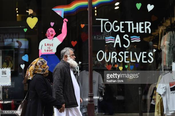 People walk past a sign saying 'together as ourselves and love is love' in Leeds City Centre on May 27, 2021 in Leeds, England.