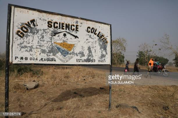 People walk past a signpost of the Government Science College where gunmen kidnapped dozens of students and staffs, in Kagara, Rafi Local Government...
