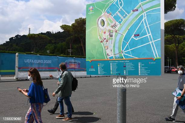 People walk past a site map on June 08, 2021 by the Olympic stadium in Rome, three days before the delayed Euro 2020 European football tournament...