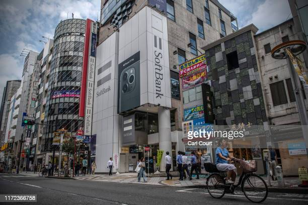 People walk past a SoftBank mobile phone store on September 30 2019 in Tokyo Japan SoftBank the technology and investment conglomerate owned by...