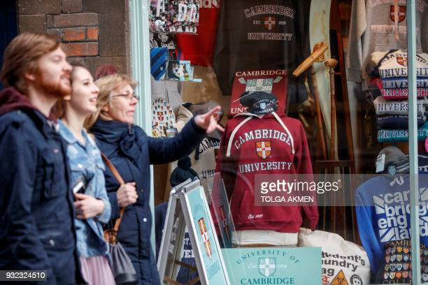 People walk past a souvenir shop selling Cambridge University branded goods in Cambridge, east of England, on March 14, 2018. / AFP PHOTO / Tolga...
