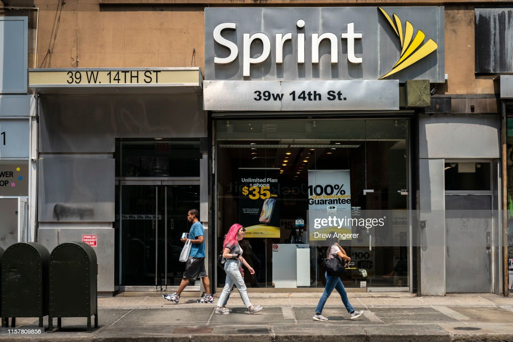 People Walk Past A Sprint On Store On 14th Street In Manhattan On