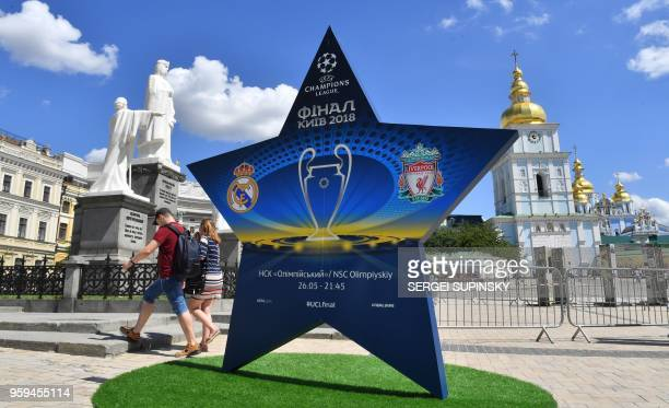 People walk past a star shaped billboard announcing the 2018 UEFA Champions League Final in the city centre of Kiev on May 17 ahead of the football...