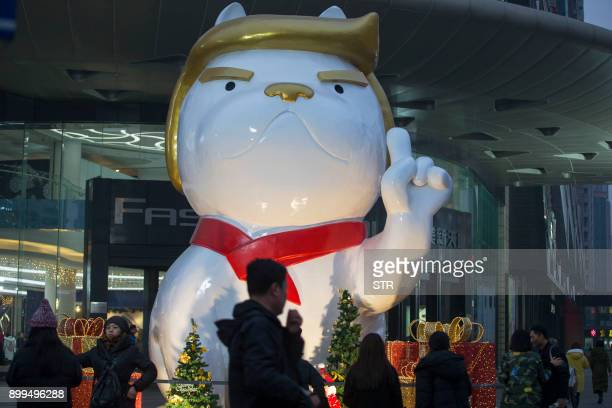 People walk past a statue of a dog with a resemblance to US President Donald Trump outside a shopping mall in Taiyuan in China's northern Shanxi...