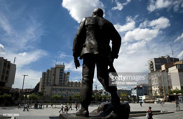 People walk past a statue of a former Kosovo Liberation Army commander in Pristina on July 29 2014 Leaders of Kosovo's 1990s guerrilla army are to be...