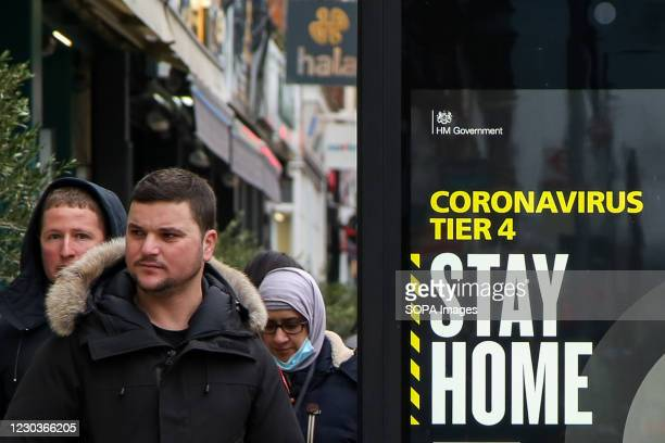 People walk past a 'Stay Home' sign in London as many parts of the UK are now under 'Stay at Home' COVID-19 Tier 4 restrictions.